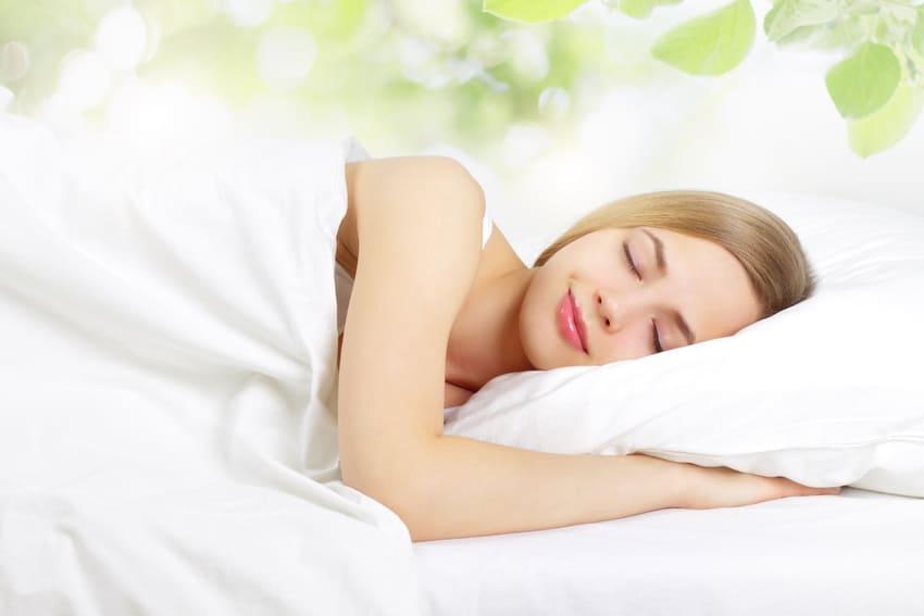 Eine Frau schläft in ihrer Gewichtsdecke
