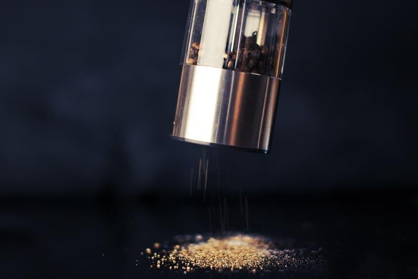Eine elektrische Pfeffermühle mahlt Pfefferkörner