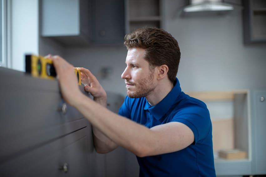 Ein Mann arbeitet mit einer digitalen Wasserwaage