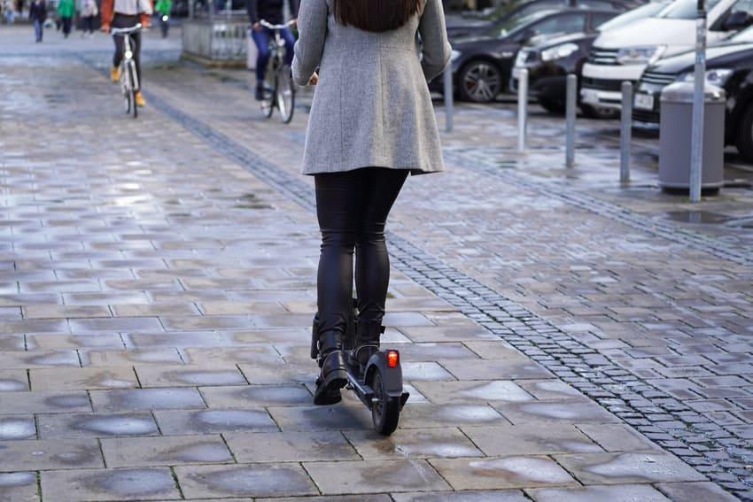 Eine Frau fährt einen E-Scooter auf der Straße