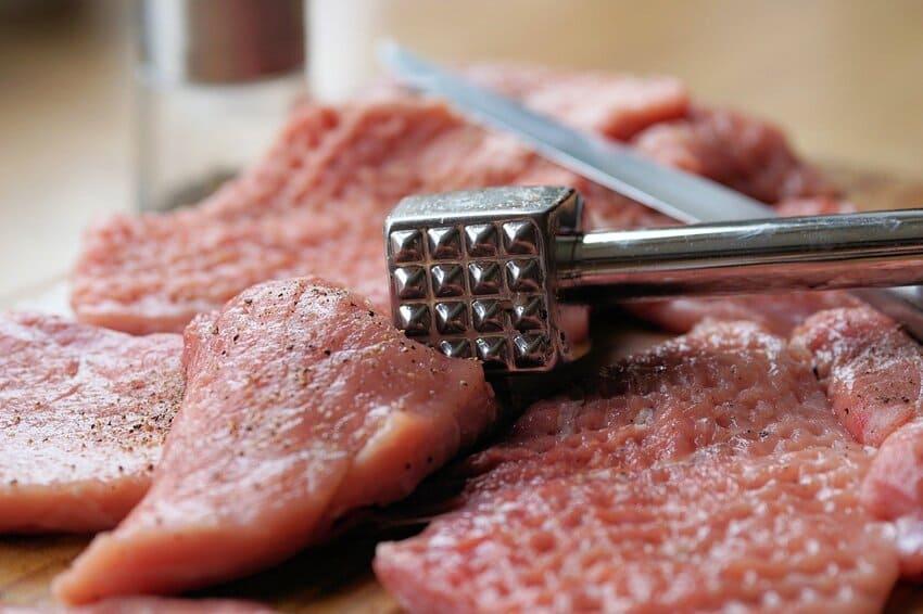 Ein Fleischklopfer aus Edelstahl liegt auf einem Steak