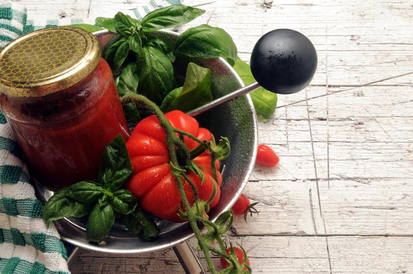 Eine Passiermühle die frische Tomaten in Soße verarbeitet