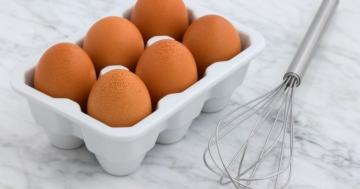 Ein Schneebesen der neben einer Eierpappe liegt