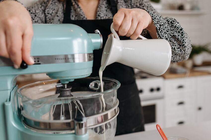 Eine Küchen Knetmaschine wird von einer Köchin benutzt