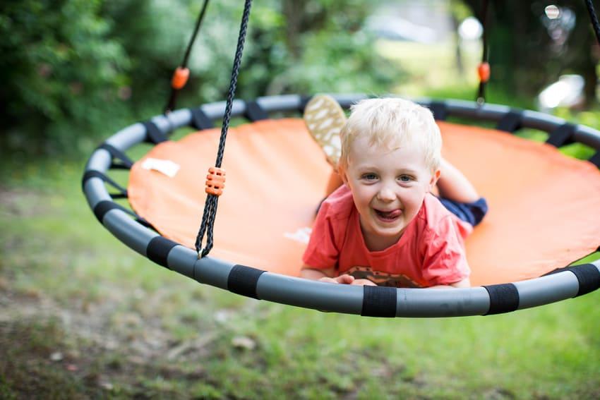 Ein Kind testet eine Nestschaukel